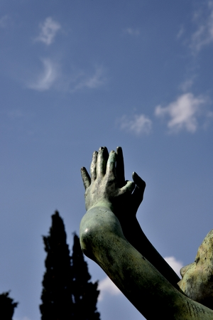 implore: Hands of statues connected That pray upwards. Detail of face. On background blue sky