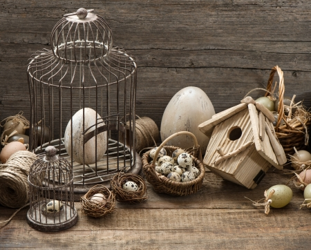 vintage easter decoration with eggs, birdhouse and birdcage  nostalgic still life home interior  wooden background photo