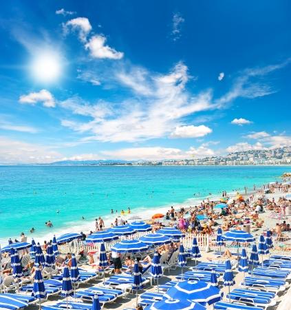 フランス、ニース プロムナード デ ザングレ、いっぱい観光客、サンベッド、パラソル夏の暑い日に近くのビーチの眺め 報道画像