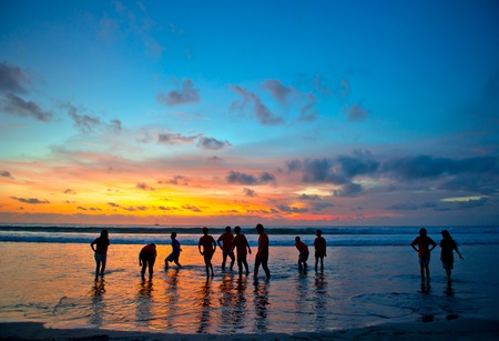 kuta: silhouettes of young people at famous sunset beach in Kuta, Bali, Indonesia