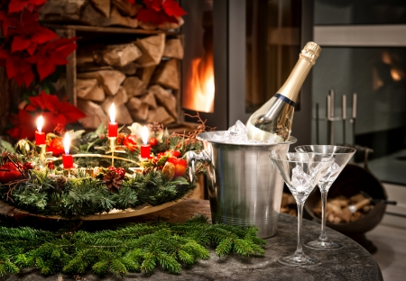 festive home interior decoration for christmas and new year with bottle of champagne and fireplace. candlelight dinner photo