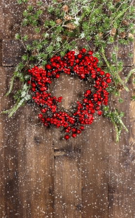 green christmas tree branches and wreath from red berries over rustic wooden background. festive decoration with snowflakes effect photo