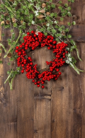 green christmas tree branches and wreath from red berries over rustic wooden background. festive home decoration photo