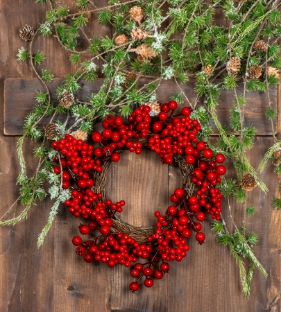 green christmas tree branches and wreath from red berries over rustic wooden background. bright festive decoration photo
