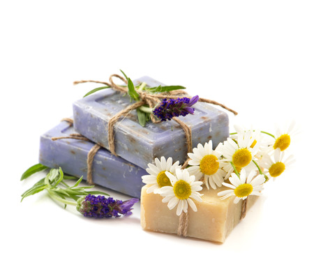 closeup of soap bars with fresh lavender and chamomile flowers isolated on white background photo