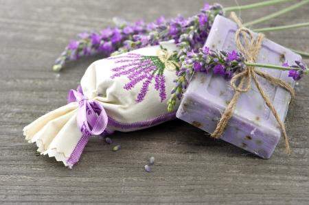 BOLSITAS PERFUMADAS: Primer plano de jabón de lavanda y perfumadas bolsitas con flores frescas sobre fondo de madera Foto de archivo