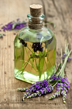essential lavender oil with fresh flowers on wooden background. selective focus photo