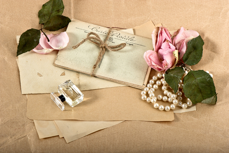 old post cards, flower, perfume and perls necklace  vintage background