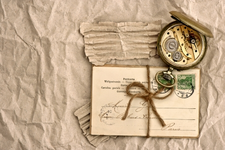 old post cards and vintage clock on grunge paper background photo