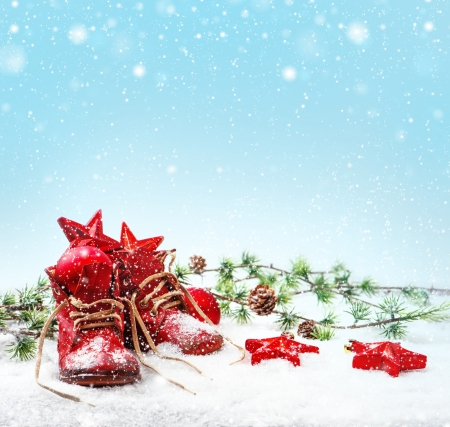 nostalgic christmas decoration with antique baby shoes  festive background  retro style picture with snow effect photo