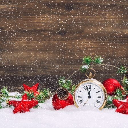 christmas decoration red stars and baubles and antique golden clock in snow over wooden background  vintage style picture with falling snow effect Stock Photo - 24280024