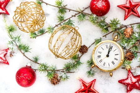 christmas decoration red stars, baubles and antique golden clock in snow over wooden background photo