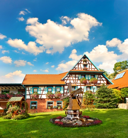 typical traditional house in the Black Forest, Southern Germany  european landscape with flowers garden and cloudy blue sky