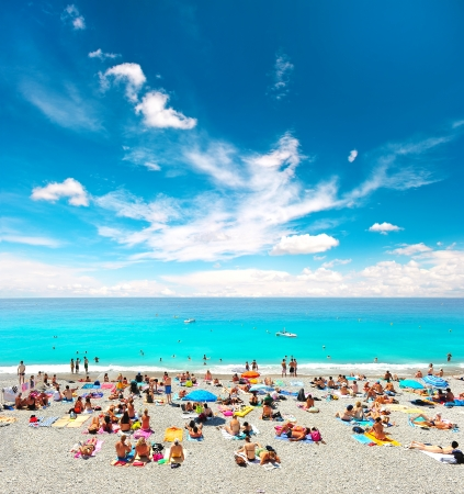 azur: View of the beach in Nice, France, near the Promenade des Anglais  tourists, sunbeds and umbrellas on summer hot day Editorial
