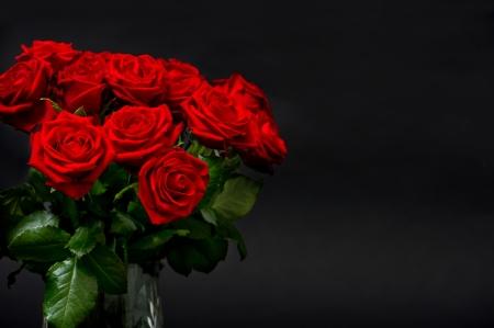 flores de cumpleaños: rosas rojas sobre fondo negro arreglo festivo Foto de archivo