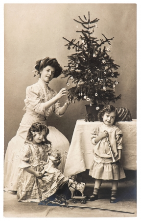 BERLIN, GERMANY - CIRCA 1900  antique family portrait of mother and children with christmas tree wearing vintage clothing, circa 1900 in Berlin, Germany