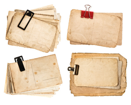stack of old postcards isolated on white background  vintage paper sheets with clip  retro design cardboards photo
