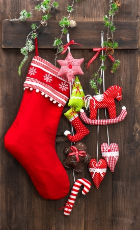 christmas decoration stocking and handmade toys over rustic wooden background photo