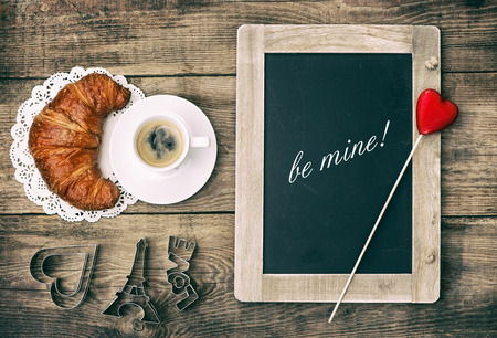 Cup of black coffee with croissant, blackboard and heart decoration on rustic wooden background photo