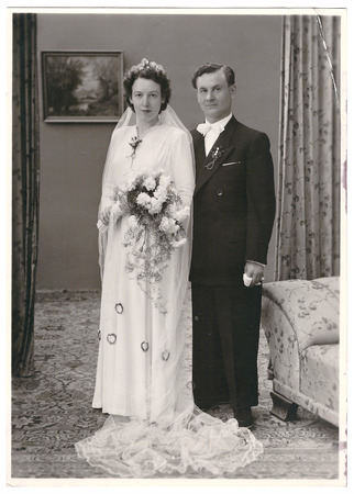 vintage wedding photo  portrait of just married couple  bride and groom wearing vintage clothing  Illustrative Image, subject of human interest  nostalgic picture with original film grain photo