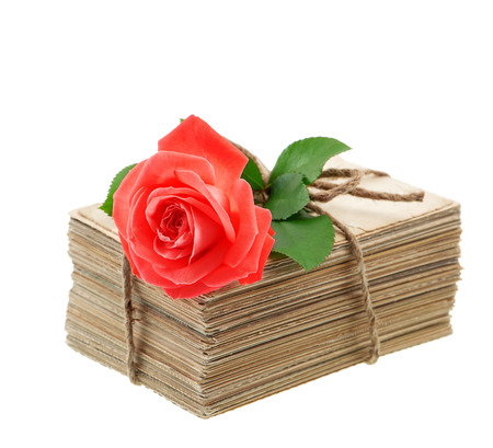 Stack of old love letters and postcards with red rose flower isolated on white background photo