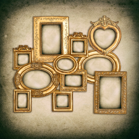 antique golden frames over grungy wall background photo
