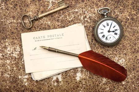 nostalgic vintage background with old post cards, clock, key and feather pen photo