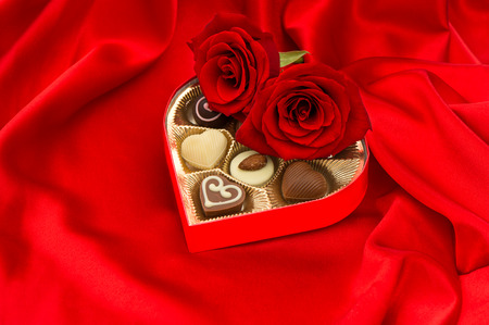 red roses and delicious chocolate pralines in golden heart shape gift box on satin  photo