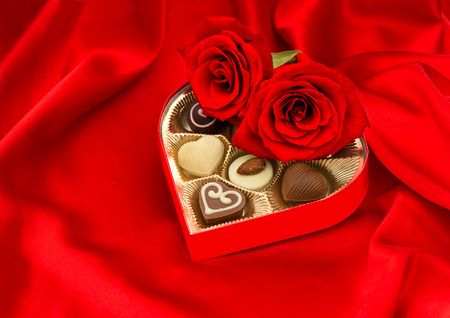 red roses and assorted chocolate pralines in golden heart shaped gift box on satin  photo