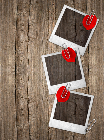 three vintage photo frames with red rose petals in heart shape over rustic wooden background photo