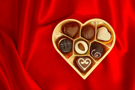 delicious chocolate pralines in golden heart shape gift box on red satin  photo
