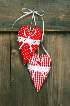 red hearts hanging over wooden background  romantic Valentines Day concept  vintage style toned picture photo