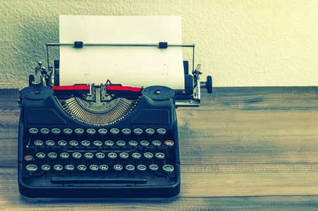 typewriter: retro typewriter with white paper page on wooden table  vintage style toned picture
