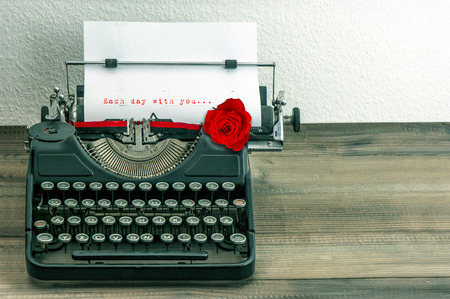 vintage typewriter with love letter and red rose flower  sample text Each day with you    photo