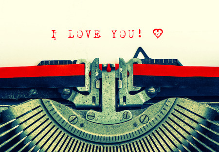 love story: Old typewriter with sample text I LOVE YOU  Red words with heart on white paper  Retro style toned picture
