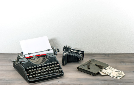 collectibles: retro typewriter and vintage photo camera on wooden table  antique objects  collectibles