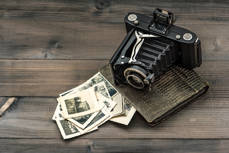 photo story: vintage camera and album with old photos on wooden table  nostalgic picture Editorial