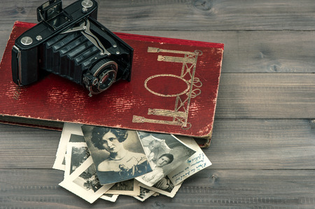 vintage camera and album with old photos on wooden table  nostalgic sentimental background