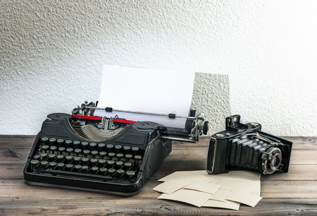collectibles: old typewriter and vintage photo camera on wooden background  antique objects  collectibles