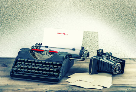 old mechanical typewriter and vintage photo camera on wooden background  antique objects  memories concept photo