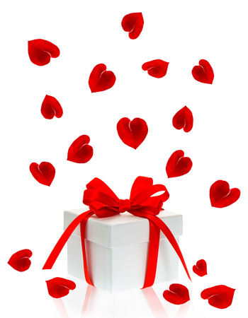 gift box with red ribbon bow and petals of rose flower in hearth shape over white background photo