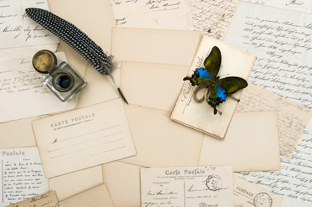 old letters: old letters, handwritings, vintage postcards and antique feather pen  nostalgic sentimental background with butterfly Stock Photo