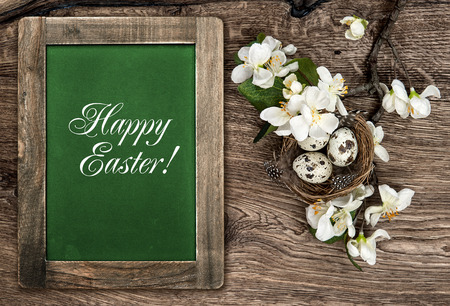 chalkboard, flowers and easter nest with eggs on rustic wooden background with sample text Happy Easter! photo