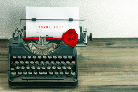 vintage typewriter with white paper page and red rose flower. sample text Thank You! photo