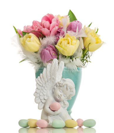 little white guardian angel with colored easter eggs and tulip flowers over white background photo