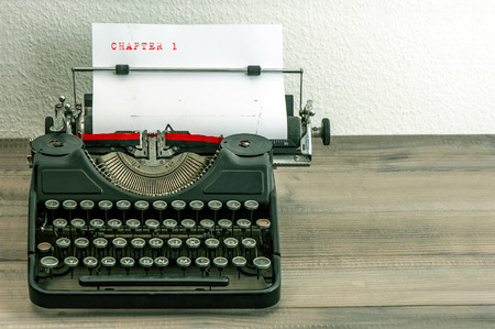 typewriter: typewriter with white paper page on wooden table. sample text Chapter 1 Stock Photo