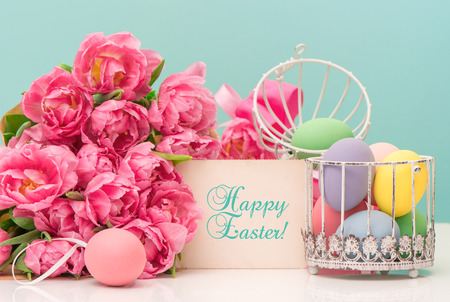 tulip flowers and pastel colored easter eggs  festive decoration with greetings card and sample text Happy Easter