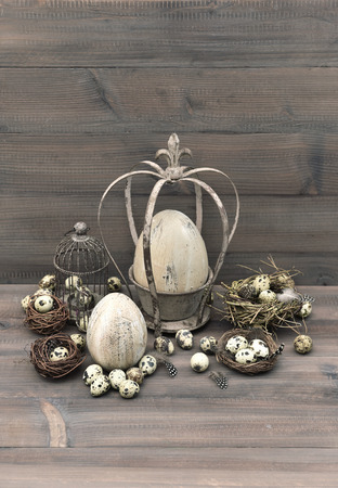 vintage easter decoration with eggs, nest and birdcage  nostalgic still life  wooden background photo
