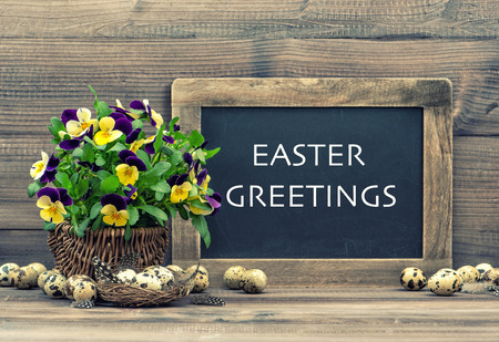 easter nest: easter decoration with eggs, pansy flowers and vintage blackboard with sample text Easter Greetings  Retro style toned picture