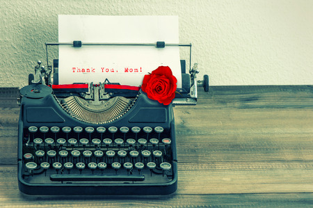 the typewriter: la m�quina de escribir de la vendimia con la p�gina en blanco y rosa roja flor de texto de ejemplo le agradece, madre de la mam�